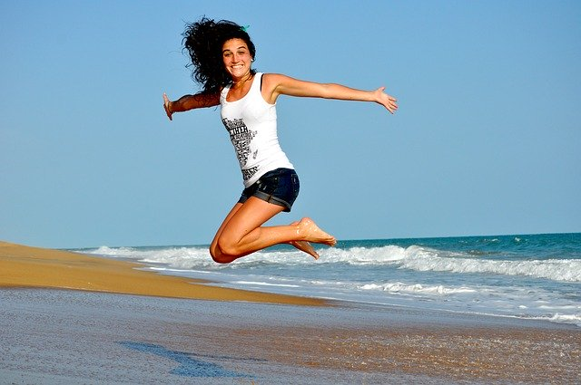 žena skáče na pláži